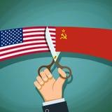 Το ανθρώπινο χέρι με το ψαλίδι κόβει την ΑΜΕΡΙΚΑΝΙΚΗ σημαία και την ΕΣΣΔ Κρύο Wa Στοκ Φωτογραφία