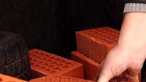 Το ανθρώπινο χέρι παίρνει τα κόκκινα τούβλα από τον κορμό του αυτοκινήτου απόθεμα βίντεο