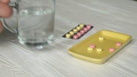 Το ανθρώπινο χέρι παίρνει τα χάπια από ένα κίτρινο εμπορευματοκιβώτιο φιλμ μικρού μήκους