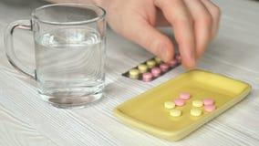 Το ανθρώπινο χέρι παίρνει τα χάπια από ένα κίτρινο εμπορευματοκιβώτιο απόθεμα βίντεο