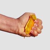 Το ανθρώπινο χέρι συμπιέζει το χυμό από το πορτοκάλι Στοκ Εικόνα