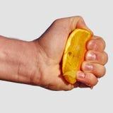 Το ανθρώπινο χέρι συμπιέζει το χυμό από το πορτοκάλι Στοκ εικόνα με δικαίωμα ελεύθερης χρήσης