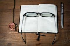 Το ανοιγμένο κενό σημειωματάριο με παλαιό αυξήθηκε, μάνδρα, eyeglass Στοκ Φωτογραφία