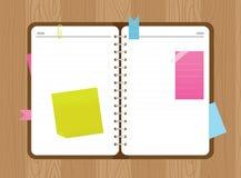Το ανοικτό ημερολόγιο τοπ άποψης με τις αυτοκόλλητες ετικέττες και ένα έγγραφο ψαλιδίζουν στο ξύλινο υπόβαθρο Στοκ Εικόνες