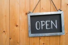 Το ανοικτό σημάδι κρεμά στην ξύλινη πόρτα Στοκ φωτογραφία με δικαίωμα ελεύθερης χρήσης