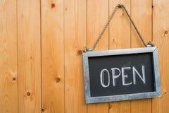 Το ανοικτό σημάδι κρεμά στην ξύλινη πόρτα Στοκ Εικόνες