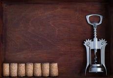 Το ανοιχτήρι και μια σειρά του ίδιου κρασιού βουλώνουν στο σκοτεινό κιβώτιο Στοκ εικόνες με δικαίωμα ελεύθερης χρήσης