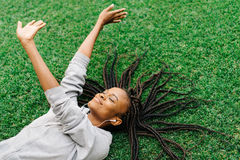 Το ανωτέρω υπαίθριο πορτρέτο του πρόθυμου gil που αυξάνει τα χέρια επάνω βάζοντας στη χλόη Η απόλαυση της μουσικής Στοκ εικόνες με δικαίωμα ελεύθερης χρήσης
