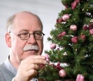 Το ανώτερο άτομο διακοσμεί το χριστουγεννιάτικο δέντρο Στοκ Εικόνα