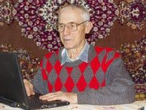 Το ανώτερο άτομο εργάζεται στο σπίτι με το lap-top και eyeglasses στοκ φωτογραφία με δικαίωμα ελεύθερης χρήσης