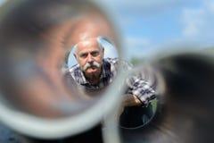 Το ανώτερο άτομο κοιτάζει μέσω των σωλήνων μετάλλων Στοκ Εικόνα