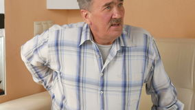 Το ανώτερο άτομο με ένα mustache δεν θα μπορούσε να κατεβεί τον καναπέ λόγω του πόνου στην πλάτη Διατηρεί τη μέση με τα χέρια του απόθεμα βίντεο