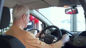 Το ανώτερο άτομο ρυθμίζει τον οπισθοσκόπο καθρέφτη μέσα στο αυτοκίνητο απόθεμα βίντεο