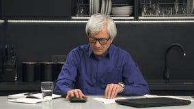 Το ανώτερο άτομο στα γυαλιά εξετάζει τις δαπάνες Στοκ εικόνες με δικαίωμα ελεύθερης χρήσης