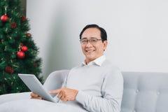 Το ανώτερο άτομο χρησιμοποιεί μια ψηφιακή ταμπλέτα και χαμογελά στηργμένος το ο στοκ φωτογραφία με δικαίωμα ελεύθερης χρήσης