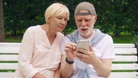 Το ανώτερο ζεύγος έχει το μεγάλο χρόνο να καθίσει στον πάγκο στο πάρκο ακούει τη μουσική στο έξυπνο τηλέφωνο μέσω των ακουστικών απόθεμα βίντεο