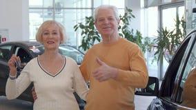 Το ανώτερο ζεύγος αγοράζει το αυτοκίνητο στον αντιπρόσωπο στοκ φωτογραφίες