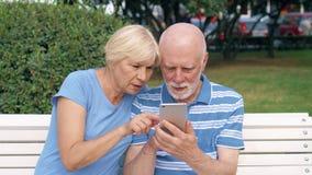 Το ανώτερο ζεύγος κάθεται στον πάγκο στο πάρκο ψάχνει την κατεύθυνση μέσω σε απευθείας σύνδεση app με το χάρτη πόλεων στο κινητό  απόθεμα βίντεο