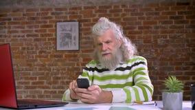 Το ανώτερο λευκό μαλλιαρό άτομο με τη μεγάλη γενειάδα κάθεται στο γραφείο τούβλου και το τηλέφωνό του, που απομονώνεται φιλμ μικρού μήκους