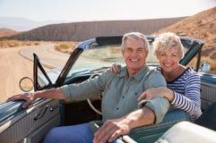 Το ανώτερο χαμόγελο ζευγών στη κάμερα από το ανοικτό τοπ αυτοκίνητο, κλείνει επάνω στοκ φωτογραφία