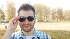 Το αξύριστο μοντέρνο άτομο με ένα όμορφο βλέμμα αυξάνει τα μάτια του και βάζει στα μαύρα γυαλιά, κινηματογράφηση σε πρώτο πλάνο,  απόθεμα βίντεο