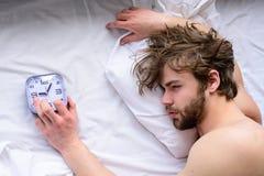 Το αξύριστο νυσταλέο πρόσωπο ατόμων βάζει τη τοπ άποψη ξυπνητηριών μαξιλαριών Πρόβλημα Oversleep Διαχειριστείτε τις κατάλληλες άκ στοκ εικόνες
