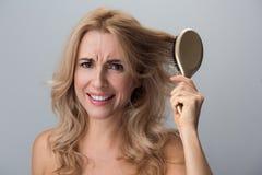 Το απογοητευμένο θηλυκό κρατά τη βούρτσα γηα τα μαλλιά και εκφράζει την ενόχληση στοκ εικόνες