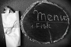 Το αποξηραμένο ψάρι είναι τυλιγμένο στο έγγραφο, είναι έπειτα μαύρος πίνακας με μέσα Στοκ Φωτογραφίες