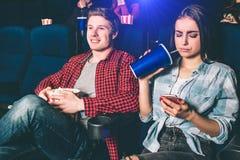 Το αποσπασμένο κορίτσι προσέχει στο τηλέφωνο Είναι βαριεστημένη με τον κινηματογράφο προσοχής Επίσης πίνει το κοκ από μεγάλος και Στοκ φωτογραφία με δικαίωμα ελεύθερης χρήσης