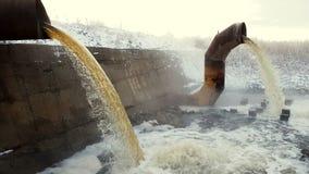 Το απόβλητο ύδωρ από τους μεγάλους σκουριασμένους σωλήνες συγχωνεύει στον ποταμό στα σύννεφα του ατμού φιλμ μικρού μήκους