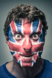 Το απόκοσμο άτομο με τη βρετανική σημαία χρωμάτισε στο πρόσωπο Στοκ Φωτογραφία