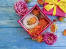 Το απόσπασμα, ουσίας δώρων όμορφος φρέσκος πορτοκαλής κρέμας σύνθεσης τόξων προϊόντων κιβωτίων καλλυντικός αυξήθηκε σε ένα μπλε ξ στοκ εικόνες
