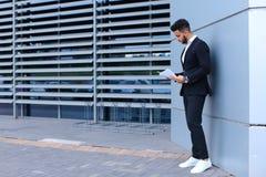 Το αραβικό άτομο επιχειρηματιών κρατά και εξετάζει, διαβάζει τα έγγραφα, s Στοκ Φωτογραφία