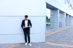 Το αραβικό άτομο επιχειρηματιών κρατά και εξετάζει, διαβάζει τα έγγραφα, s Στοκ Εικόνες