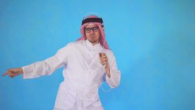 Το αραβικό άτομο στα ακουστικά στέκεται σε ένα μπλε υπόβαθρο και σθεναρά το χορό στη μουσική απόθεμα βίντεο