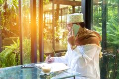 Το αραβικό μουσουλμανικό έξυπνο τηλέφωνο χρήσης ατόμων, φαίνεται έξω μεγάλο παράθυρο και γράφει το ο Στοκ Εικόνες