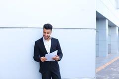 Το αραβικό όμορφο χαμόγελο σπουδαστών, κρατά και εξετάζει τα έγγραφα ν στοκ εικόνες