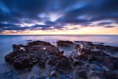 Το αργά το βράδυ τοπίο του ωκεανού πέρα από τη δύσκολη ακτή βαριά καλύπτει το BL Στοκ Εικόνες