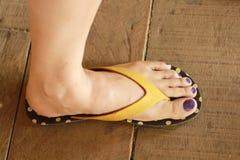 Το αριστερό πόδι της γυναίκας φόρεσε τη στάση σανδαλιών στο ξύλινο πάτωμα Στοκ Φωτογραφίες