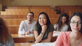 Το αρκετά ασιατικό κορίτσι αυξάνει το χέρι και υποβάλλοντας την ερώτηση κατά τη διάρκεια της διάλεξης στο κολλέγιο, οι συμμαθητές απόθεμα βίντεο