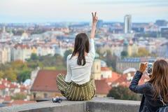 Το αρκετά ασιατικό κορίτσι θέτει και εξετάζει την παλαιά πόλη της Πράγας από τις γέφυρες παρατήρησης κοντά στο Κάστρο της Πράγας, στοκ εικόνες