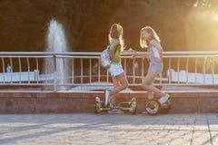 το αρκετά ευτυχές κορίτσι δύο που οδηγά αιωρείται τον πίνακα ή gyroscooter υπαίθρια στο ηλιοβασίλεμα το καλοκαίρι Ενεργός έννοια  στοκ φωτογραφίες με δικαίωμα ελεύθερης χρήσης