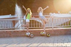 το αρκετά ευτυχές κορίτσι δύο που οδηγά αιωρείται τον πίνακα ή gyroscooter υπαίθρια στο ηλιοβασίλεμα το καλοκαίρι Ενεργός έννοια  στοκ εικόνα με δικαίωμα ελεύθερης χρήσης