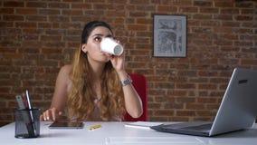 Το αρκετά καυκάσιο θηλυκό η ταμπλέτα της και πίνει τον καφέ από το άσπρο φλυτζάνι, που απομονώνεται στο στούντιο τούβλου φιλμ μικρού μήκους