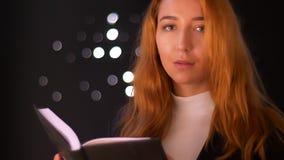 Το αρκετά καυκάσιο θηλυκό πιπεροριζών στέκεται και διαβάζει το βιβλίο με τη συγκέντρωση στο μαύρο φωτεινό στούντιο και κοιτάζει  απόθεμα βίντεο