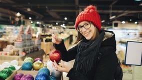 Το αρκετά καυκάσιο κορίτσι στα γυαλιά και ένα κόκκινο καπέλο επιλέγει τις σφαίρες για τα Χριστούγεννα στην αγορά και το παιχνίδι  φιλμ μικρού μήκους