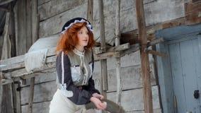 Το αρκετά κοκκινομάλλες κορίτσι υπερασπίζεται την παλαιά ξύλινη καλύβα και ρίχνει επάνω στους σπόρους καλαμποκιού απόθεμα βίντεο