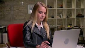 Το αρκετά ξανθό καυκάσιο κορίτσι εξετάζει τη οθόνη υπολογιστή με τη συγκέντρωση και καταψύχει στο γραφείο τούβλου καθμένος απόθεμα βίντεο