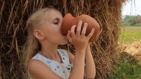 Το αρκετά ξανθό κορίτσι πίνει το φρέσκο γάλα αγελάδων ` s από μια κανάτα αργίλου ενάντια στη θυμωνιά χόρτου το καλοκαίρι στο αγρό απόθεμα βίντεο
