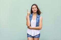 Το αρκετά περιστασιακό κορίτσι ύφους με τις φακίδες πήρε την ιδέα και αύξησε το δάχτυλό της επάνω και σκεπτόμενος Στοκ Φωτογραφίες